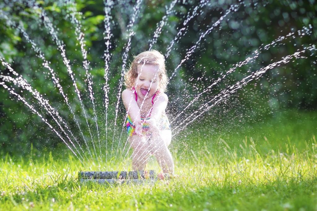 Little girl playing with garden sprinkler