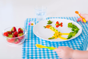 Healthy vegetarian lunch for little kids. Kid meal. Vegetable and fruit served as animals, corn, broccoli, carrot, strawberry helping child to learn eating right and clean, children hands with spoon