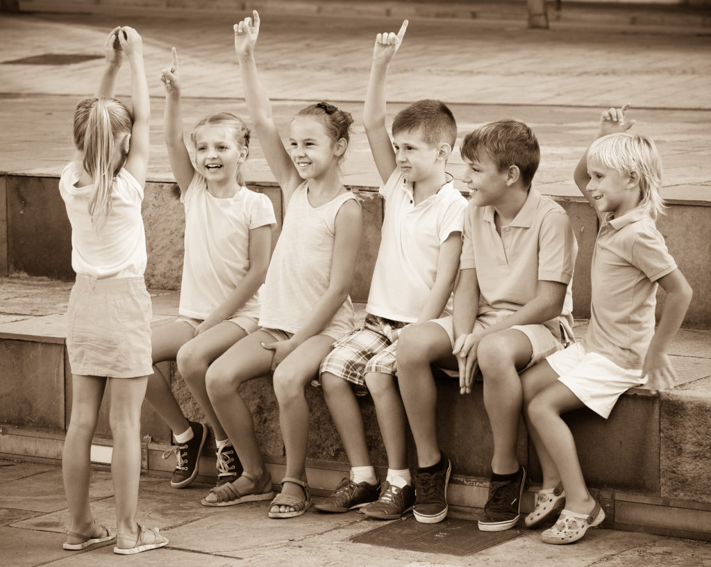 Positive boys and girls in school age having fun playing charades