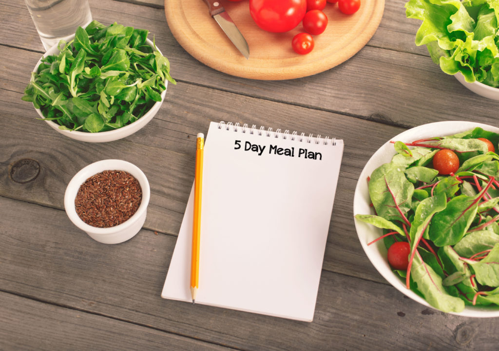 Blank notebook with various salad leaves, glass of water, tomatos and flax seed. Helpful balanced diet, weight loss and diet concept, top view