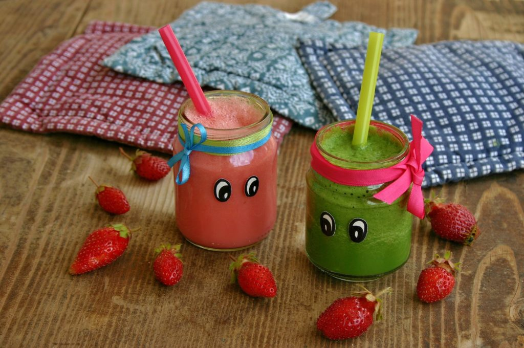 green smoothies with strawberries in the background