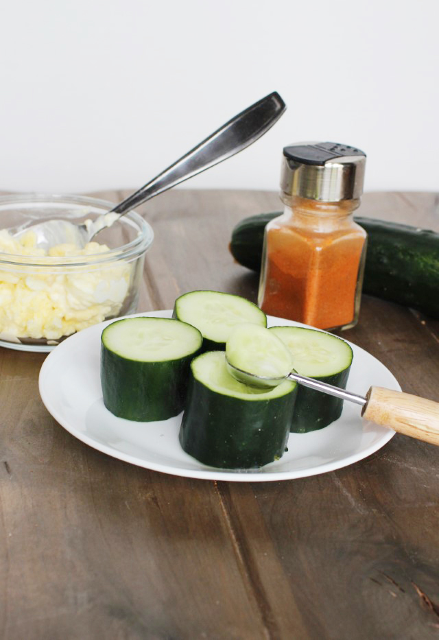 Scooping out the middle of a cucumber for cucumber cups.