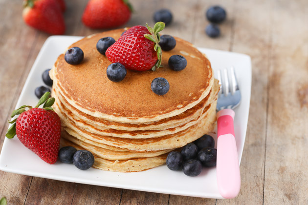 Close up of cottage cheese protein pancakes stacked on a plate with strawberries and blueberries