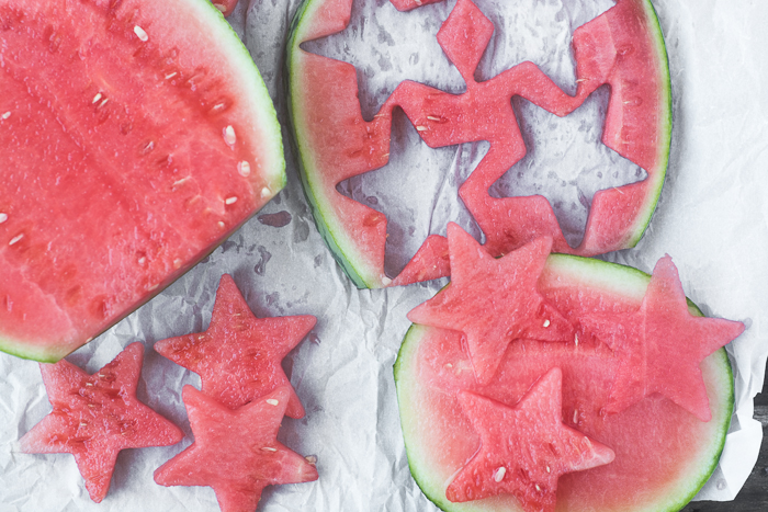 Cutting watermelon stars for a healthy red white and blue themed infused water for the 4th