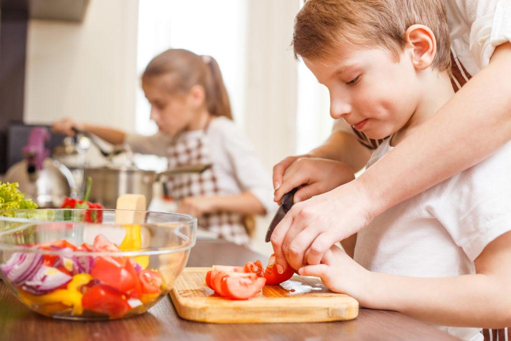 boy learning to slice veggies