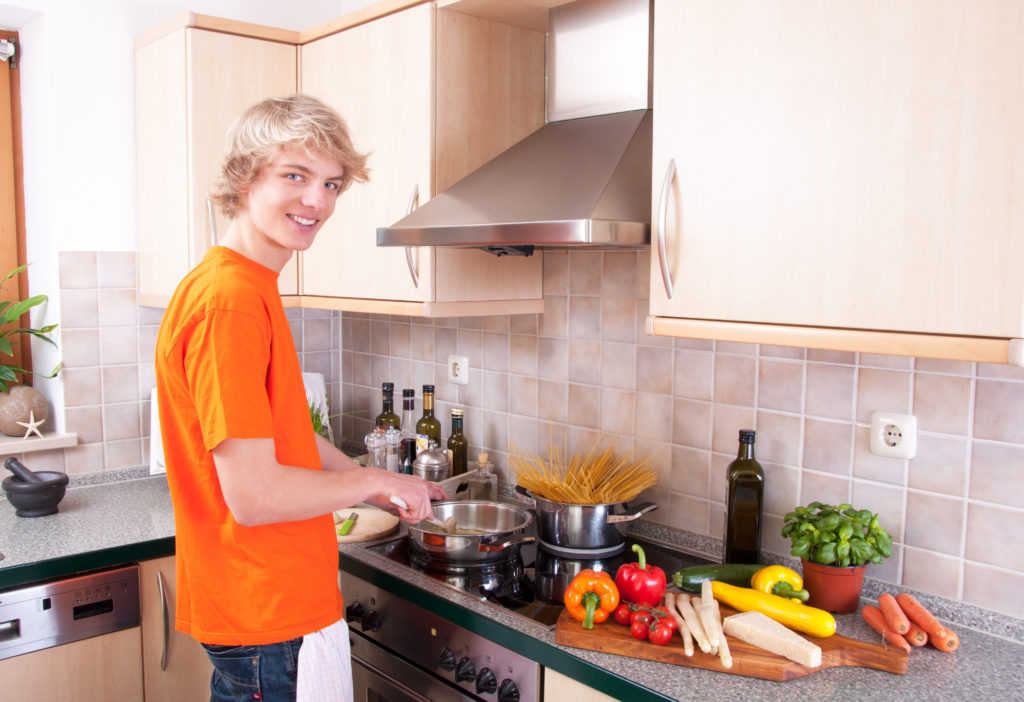 teenager boy learning to cook
