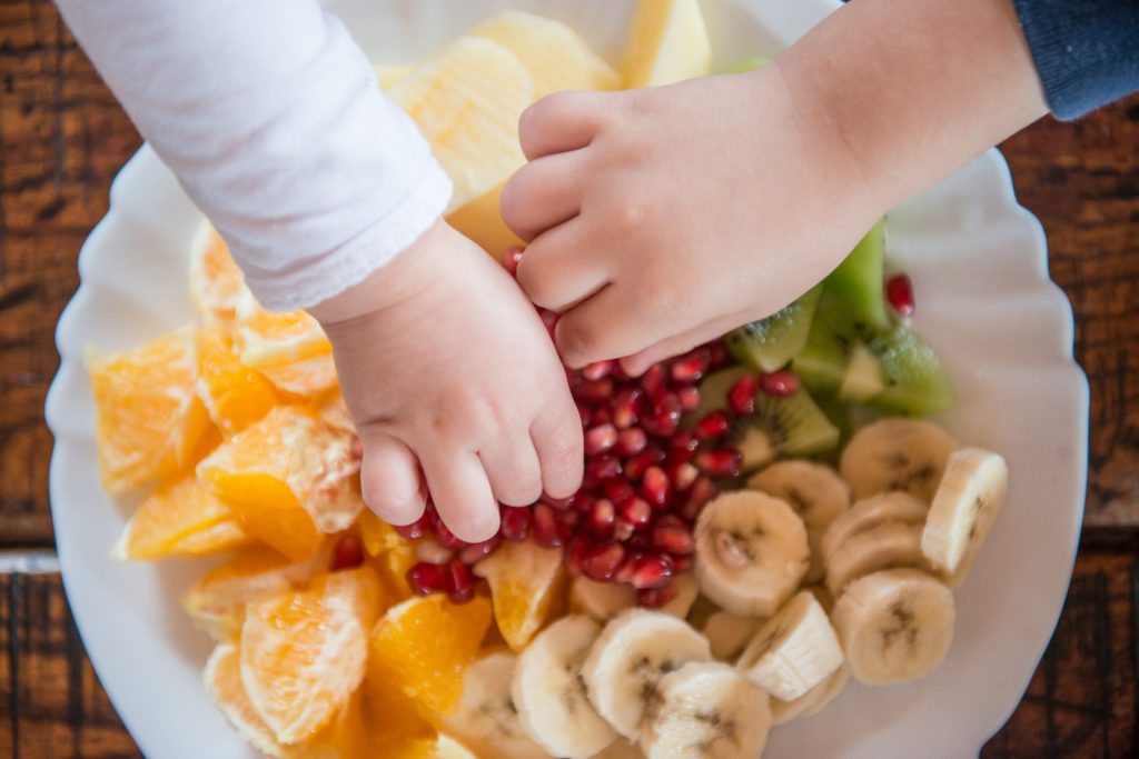 Healthy Snacking for Toddlers - Fruit and Veggie Healthy Snacks for Toddlers, toddlers grabbing cut up fruits from a bowl