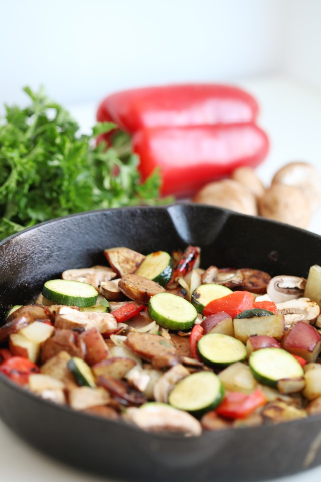 a cast iron skillet with vegetables and sausage