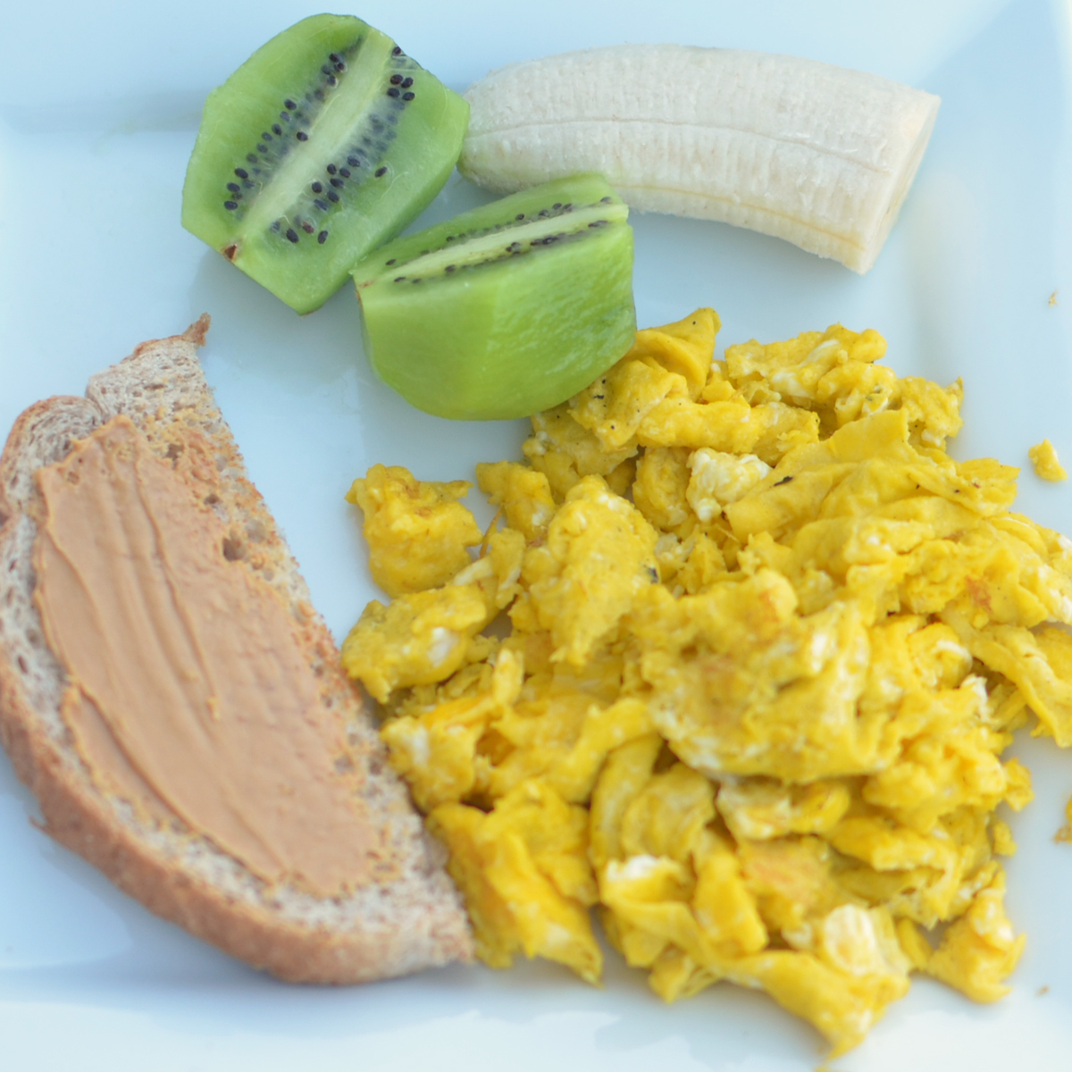 Scrambled Eggs With Peanut Butter Toast And Kiwi